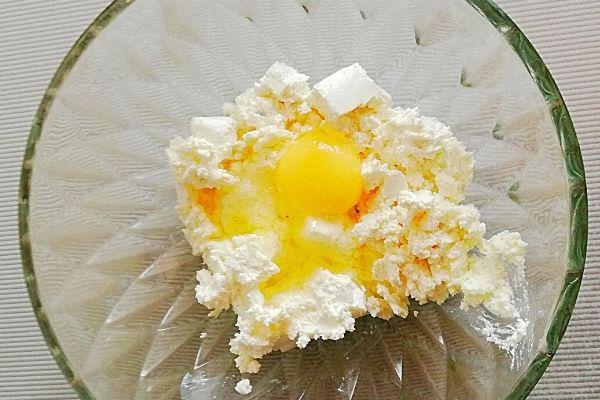 Разминаем творог, добавляем яйцо и сахар