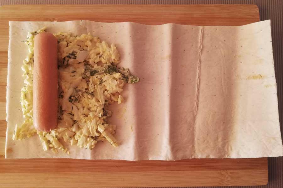 На лаваш выкладываем начинку и сосиску, заворачиваем рулетом